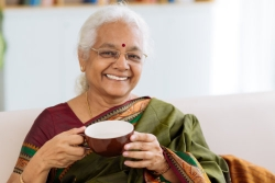 cheerful indian lady holding a cup