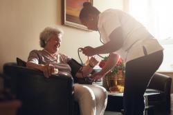 nurse measuring blood pressure of senior women patient